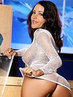 Rita G standing at bar in tiny white fishnet dress