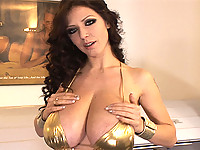 Merilyn oils up her tits in gold bikini